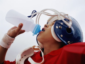 A youth football plaeyer drinking water with his shoulder pads and helmet on. Benefits of Hydration during Exercise