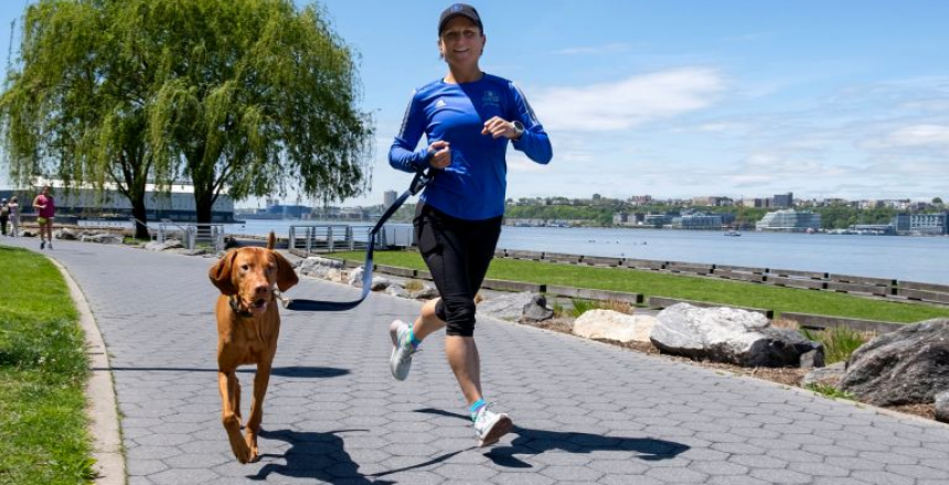 A medium-sized dog running with its owner on a riverfront. Pet hydration is always important during physical activity.